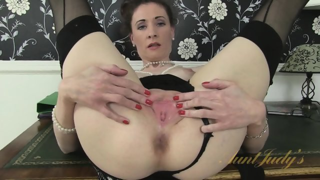 Mature slag in stockings climbed on a table