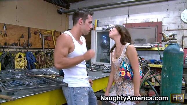 Muscular dude in a garage having fun with a brunette